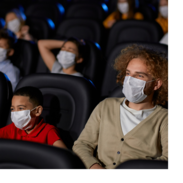 A boy and a man sit together in a movie theater and enjoy a movie. They are wearing masks.