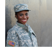 A woman wearing military fatigues stands against a wall and smiles.