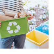 A woman carries a basket of items to be recycled. Behind her are various trash bins and a pile of waste.