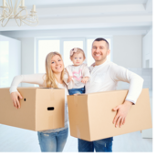 A smiling man and a woman hold their daughter between them. They hold cardboard boxes and stand in an empty apartment.