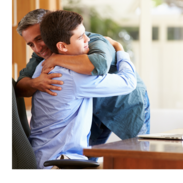 A young man sits at a table in an office chair. He smiles as he is hugged by his father.