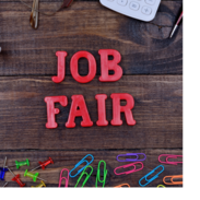 """The words, """"job fair,"""" sit on a table surround by thumb tacks, paperclips, a calculator and pens."""