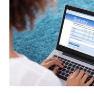 A woman takes an online survey using a laptop.