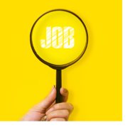 "A hand holds a magnifying glass over the word ""job."""