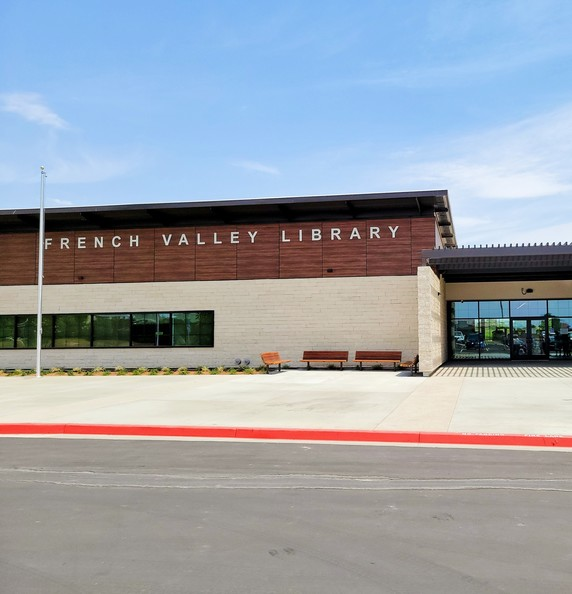 """A brown-and-white building against a blue sky. The building says """"French Valley Library"""" on the outside."""
