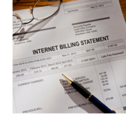 A pen and pair of glasses sitting on an internet billing statement.