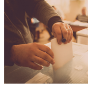 A man holding a pen puts a ballot into a box.