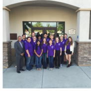 Supervisor Washington stands next to a group of teenagers in purple shirts.