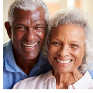 A smiling older man and older woman poses for a photo together