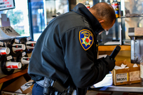 Officer in a store, looking at the cash box with a flashlight