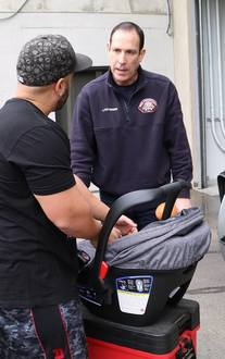 Roseville Fire employee talking to a dad with a car safety seat
