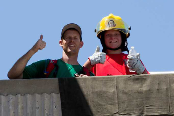 Firefighter and kid in fire helmet, thumbs up