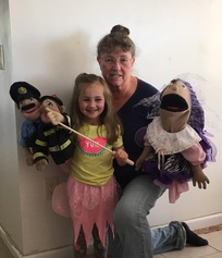 Storyteller Miss Roz with little girl and police puppets