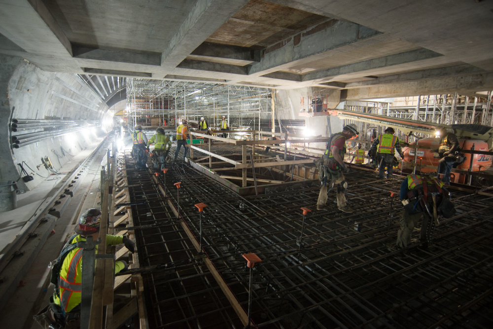 Workers put the finishing touches on rebar installation to complete construction of the Chinatown Station platform slab.