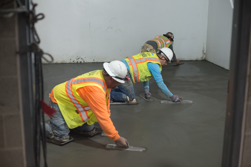 A crew smooths out the finished floor slab for interior rooms inside the station headhouse.