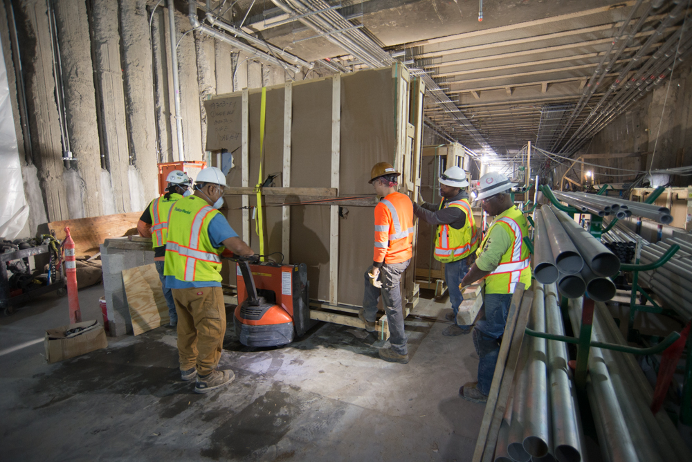 A crew carefully moves massive crates containing interior design elements for Union Square/Market Street Station.
