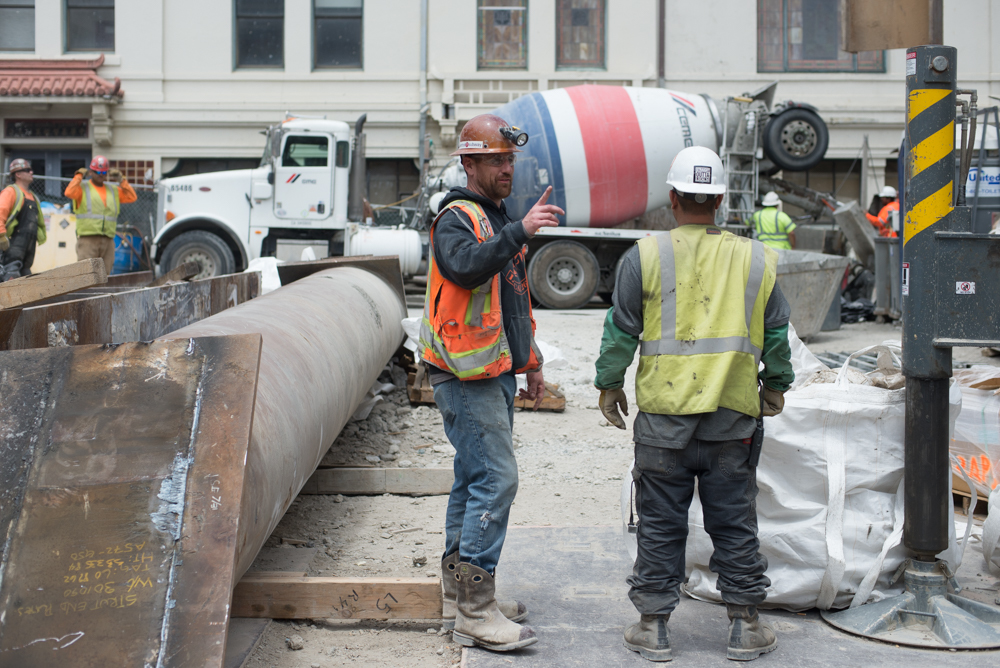 Workers discuss operations while associates pour concrete into a pump atop the Chinatown Station headhouse site.