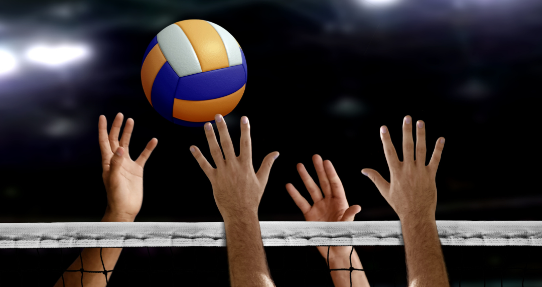 Photo of volleyball and four hands above a net