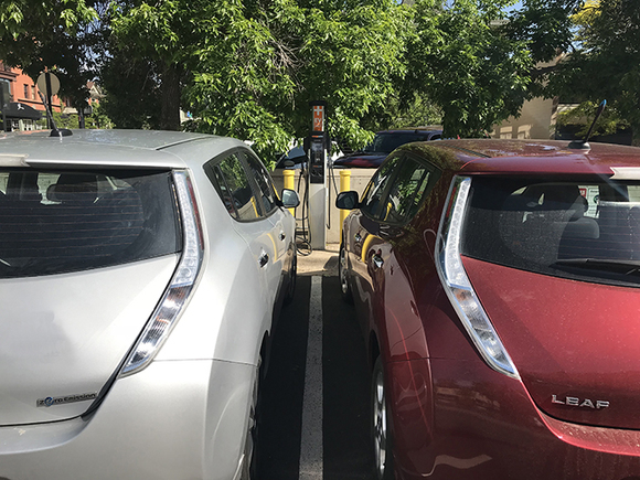 Two passenger electric vehicles plugged in and charging at an EV charging station in the Boulder County parking lot