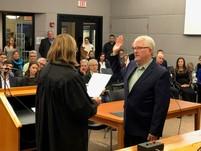 Commissioner Matt Jones being sworn into office
