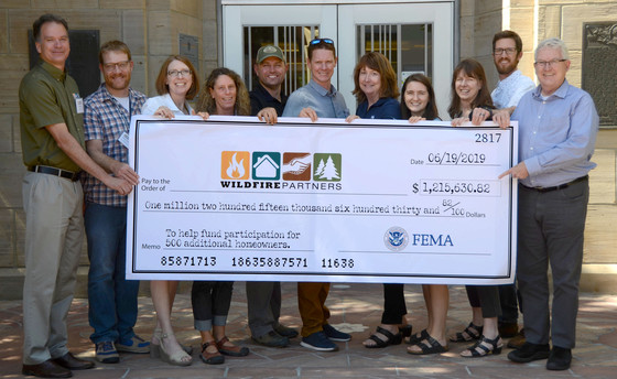 Wildfire Partners committee holding large check
