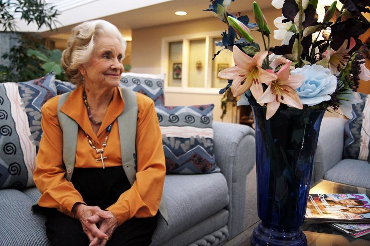 Older adult woman in a lobby of a retirement facility