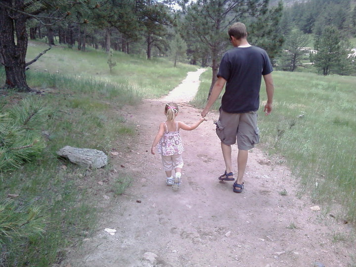 Dad and daughter holding hands hiking on trail
