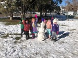 Boulder Day Nursery kids outside playing next to a snowman