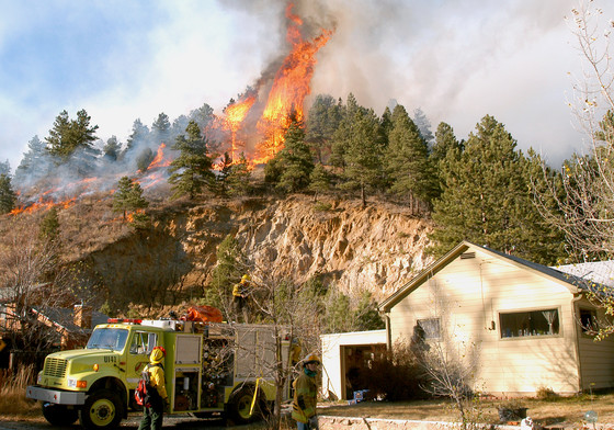 Firefighters defend a house from a wildfire