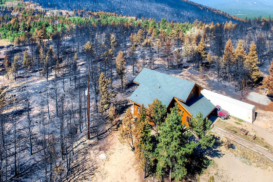 House that survived a wildfire due to establishing defensible space around the perimeter