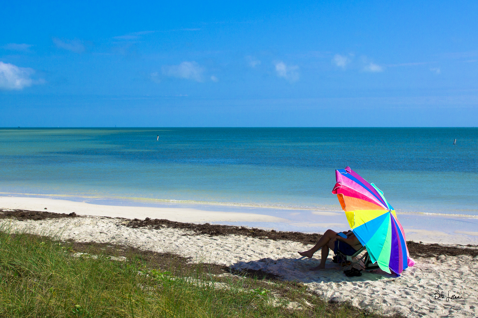 A person relaxes under an umbrella at Bahia Honda State Park