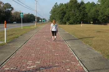 walker on red brick multi-use path near Milton, part of Old Spanish Trail, by Doug Alderson
