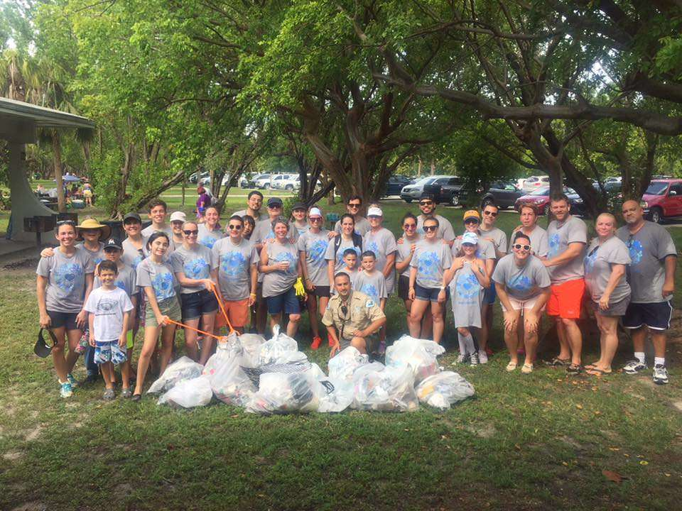 Group of Norwegian Cruise Line employees and park ranger stand behind bags of trash collected during event.