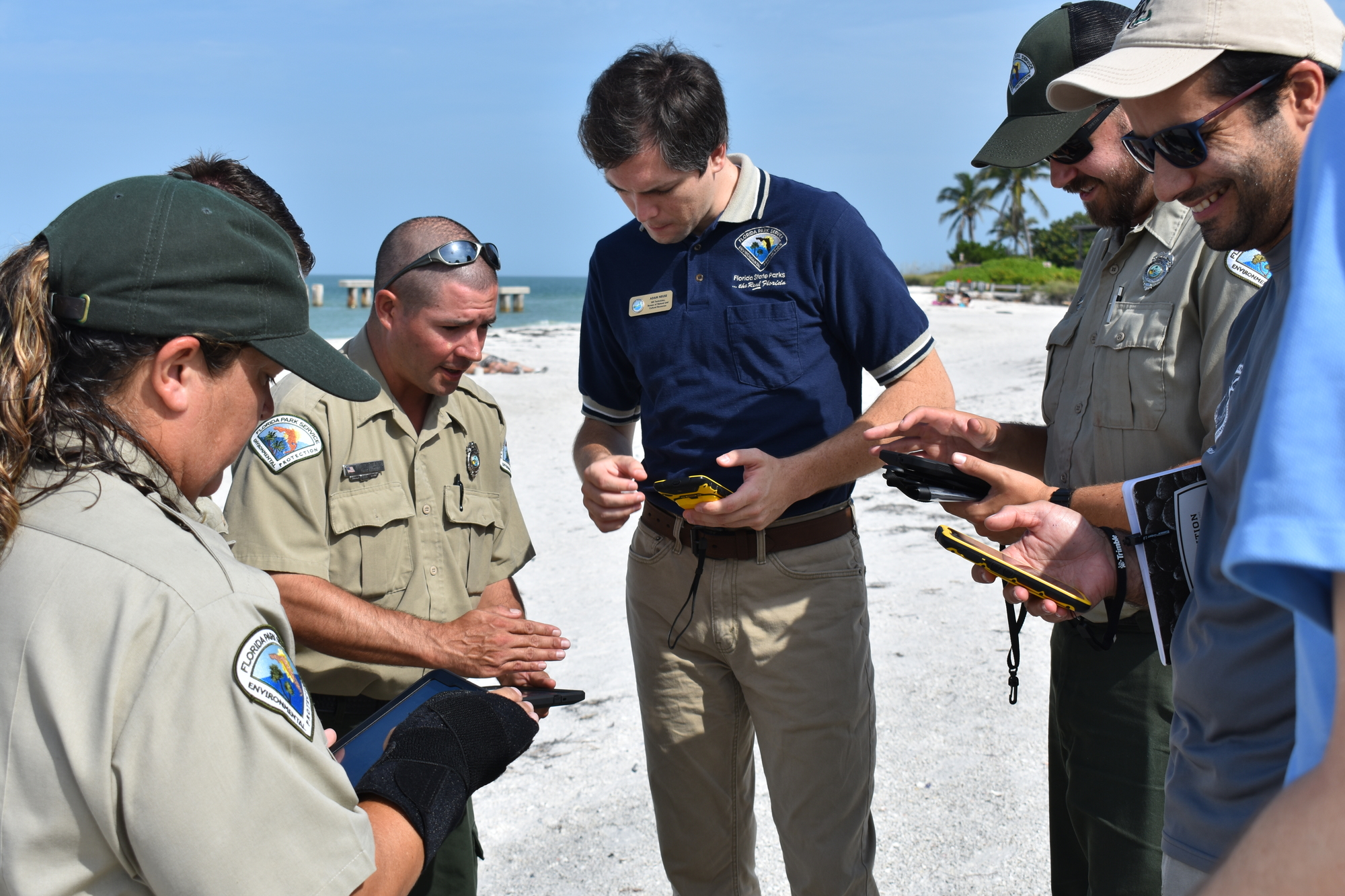 Standing on a beach, GIS technician shows park staff how to use mobile app to survey sea turtle nests.