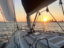 The front of a sailboat on the bay with the setting sun over a distant city