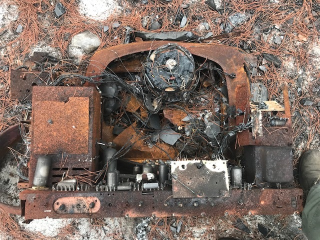 The inner contents of the back end of a television. Four televisions were found at the site.