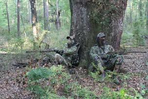 Turkey hunters sitting at base of large tree