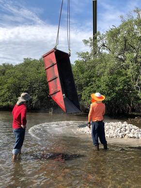 Contractors using a crane to lift limestone