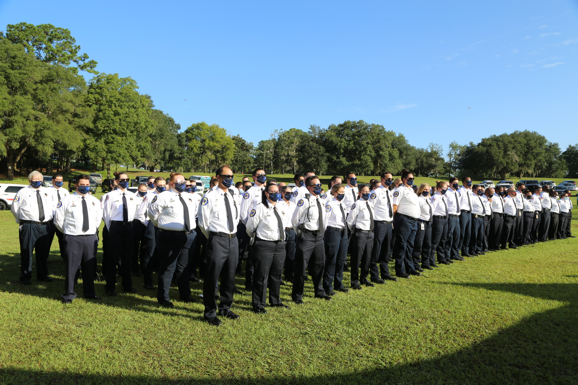 Group of first responders stand at attention in Tom Brown Park
