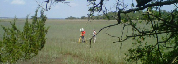 Archaeologists using scanners on a marsh