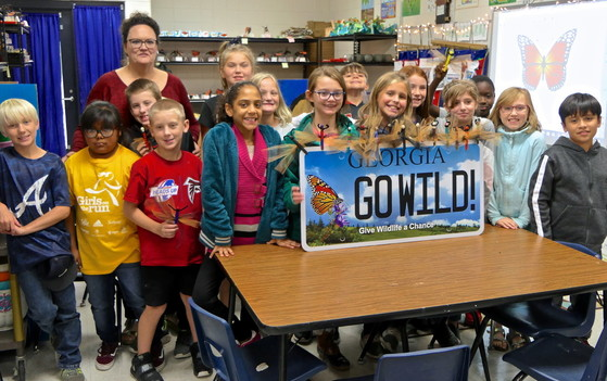 Teacher Stephanie Hodges poses with students and a DNR pollinator plate (Linda May/DNR)