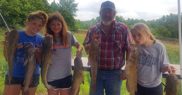 Three teenage girls and a man holding catfish.