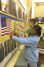 Young girl standing in front of flag on bulletin board