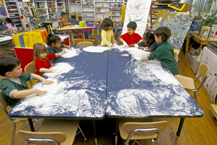 Preschool children at large tables finger painting