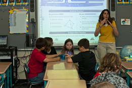 Teacher instructing elementary students in math, geometry.