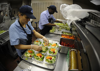 School cafeteria staff preparing vegetable salads for students