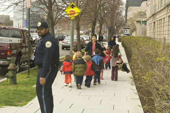 Children exiting on sidewalk, police officer nearby