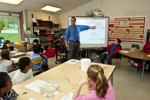 Male teacher at white board teaching a math lesson