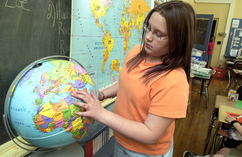 Student pointing to a place on a globe