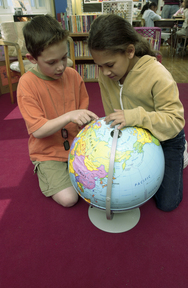 Students looking at globe